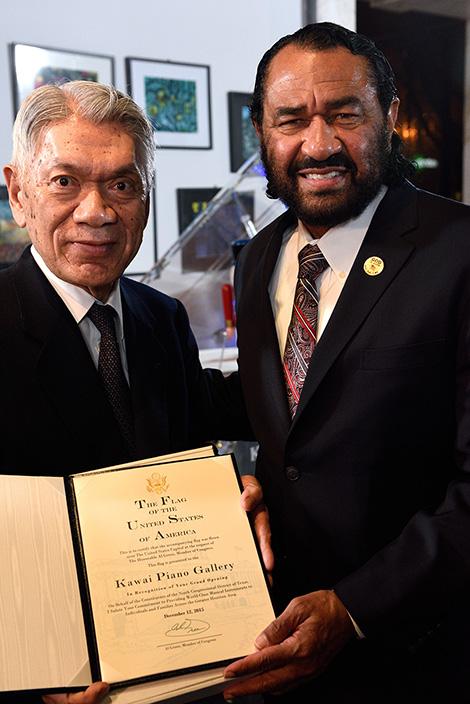 栄誉証書を手にする河合会長兼社長(左)と米下院議員のアル・グリーン氏(右)